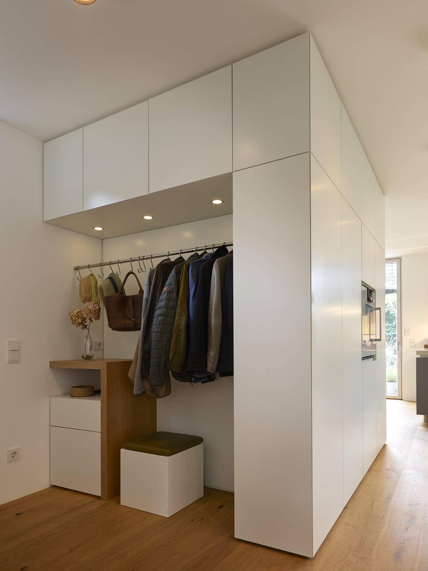 Küchendesign von VOIT in Eiche Natur mit BetonART und Edelstahl - Diele mit Garderobe mit Kleidungsstücken