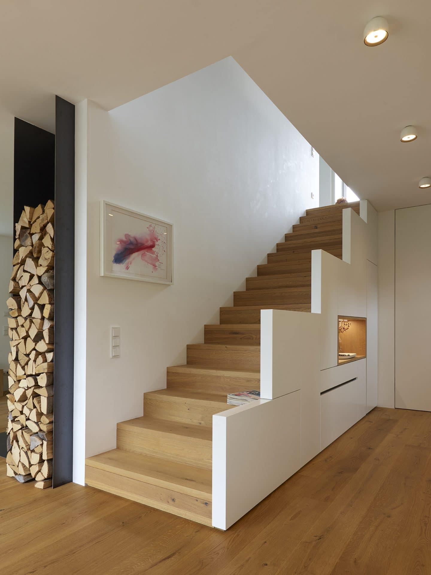 Küchendesign von VOIT in Eiche Natur mit BetonART und Edelstahl - Holztreppe aus Eiche, links daneben Brennholzhalter aus Metal