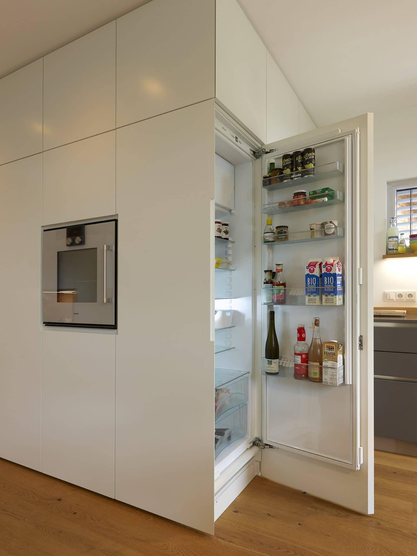 Küchendesign von VOIT in Eiche Natur mit BetonART und Edelstahl - Kühlschrank geöffnet, links ums Eck Einbaugerät