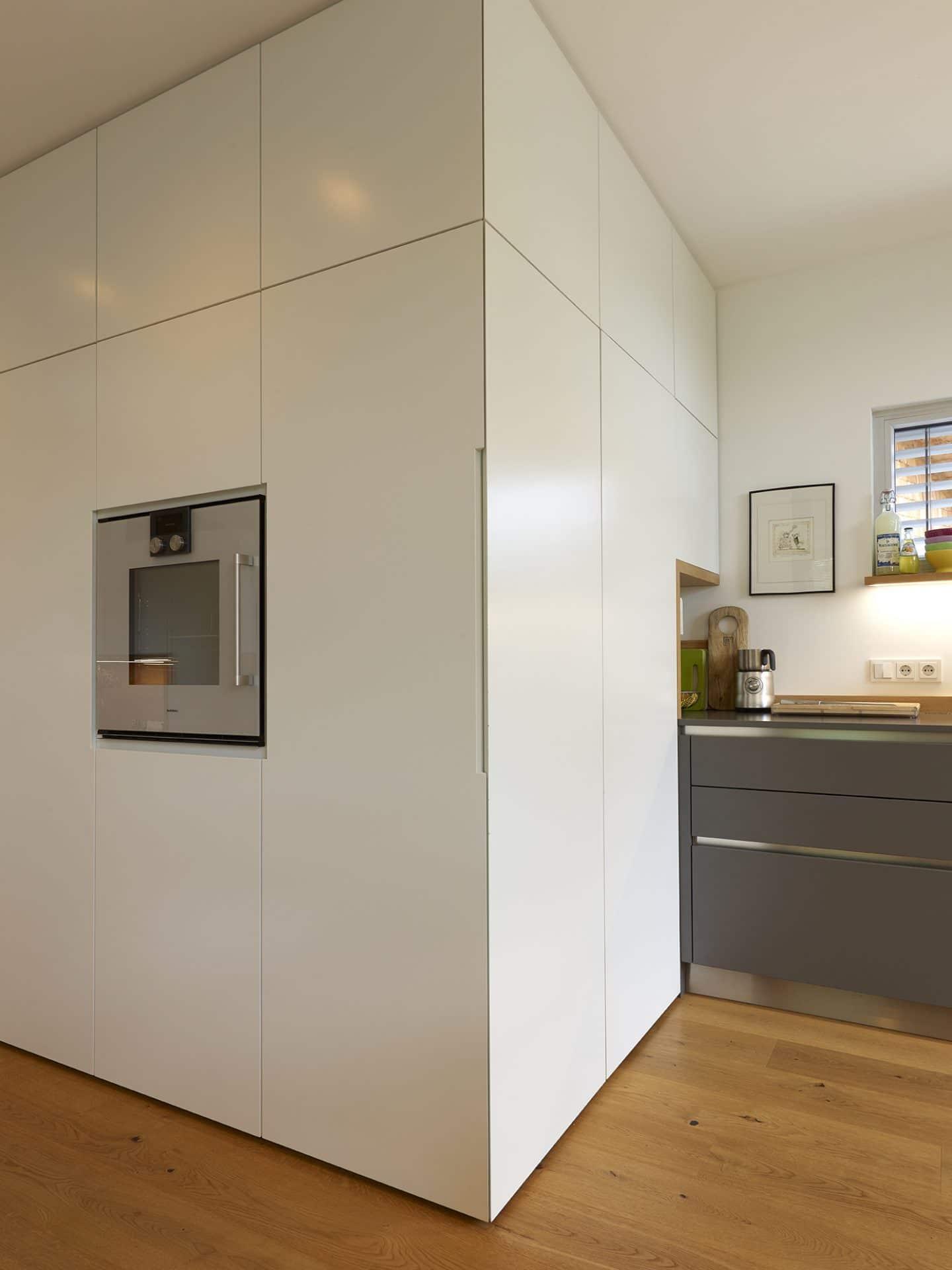 Küchendesign von VOIT in Eiche Natur mit BetonART und Edelstahl - Kühlschrank geschlossen, links ums Eck Einbaugerät
