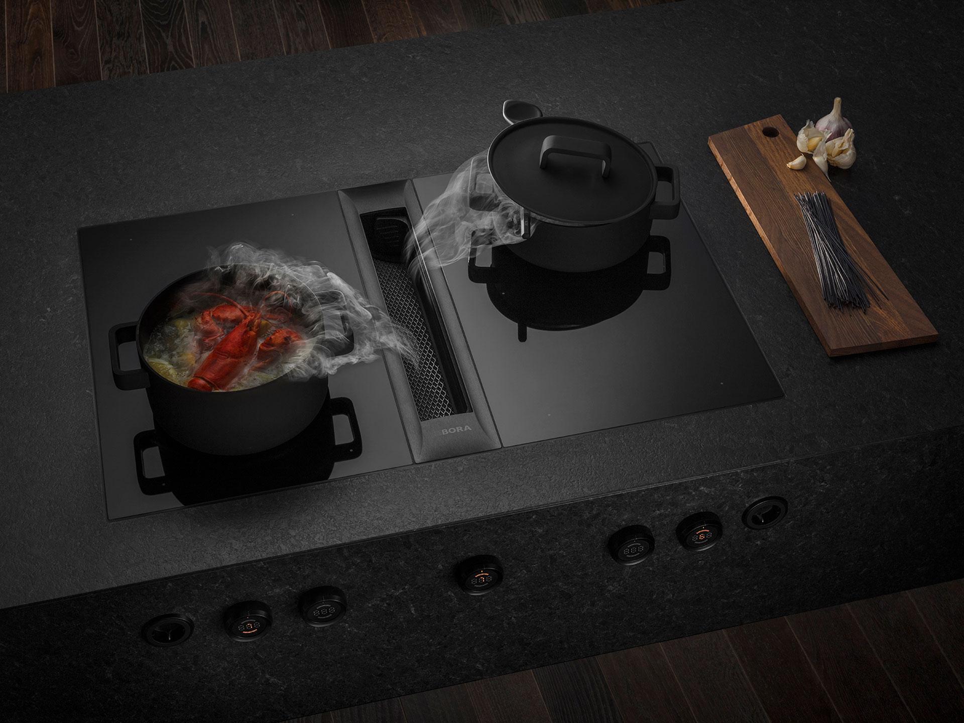 Dunstabzugsystems BORA PROFESSIONAL 3.0 in einer dunklen Granitarbeitsplatte verbaut mit zwei Kochtöpfen darauf