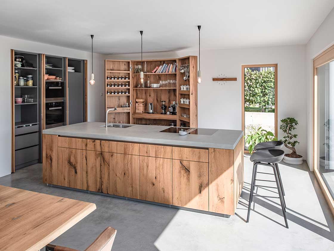 Kücheninsel mit Fronten aus rustikaler Eiche und einer Betonarbeitsplatte, im Hintergrund geöffnete Küchenschränke