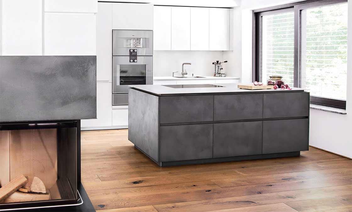 Kücheninsel mit schwarzen Steinfronten und weißen Schrankfronten im Hintergrund