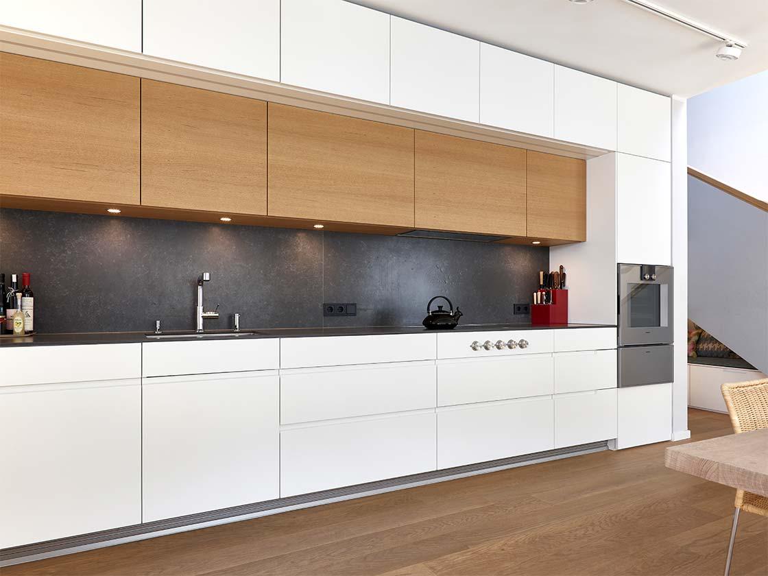 Küchenzeile mit weißen Fronten und Eichenholz Hängeschränken