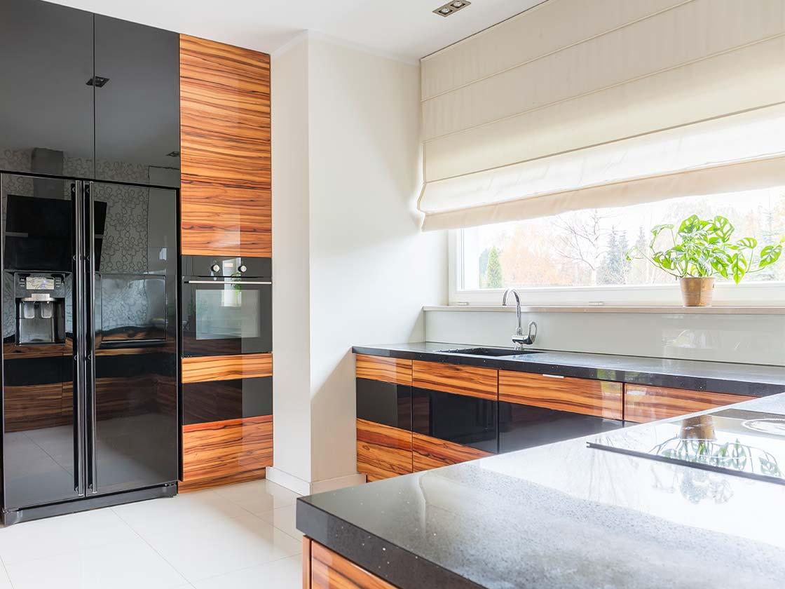 Eckküche mit rötlichen Fronten kombiniert mit Schwarzen Einbaugeräten und einer schwarzen Steinarbeitsplatte
