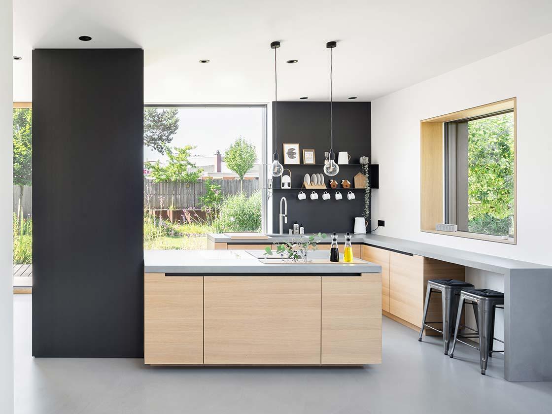 U-Küche mit hellen Holzfronten und einer individuellen Schranklösung in schwarz, Arbeitsplatte aus Beton mit Blick in den Garten im Hintergrund