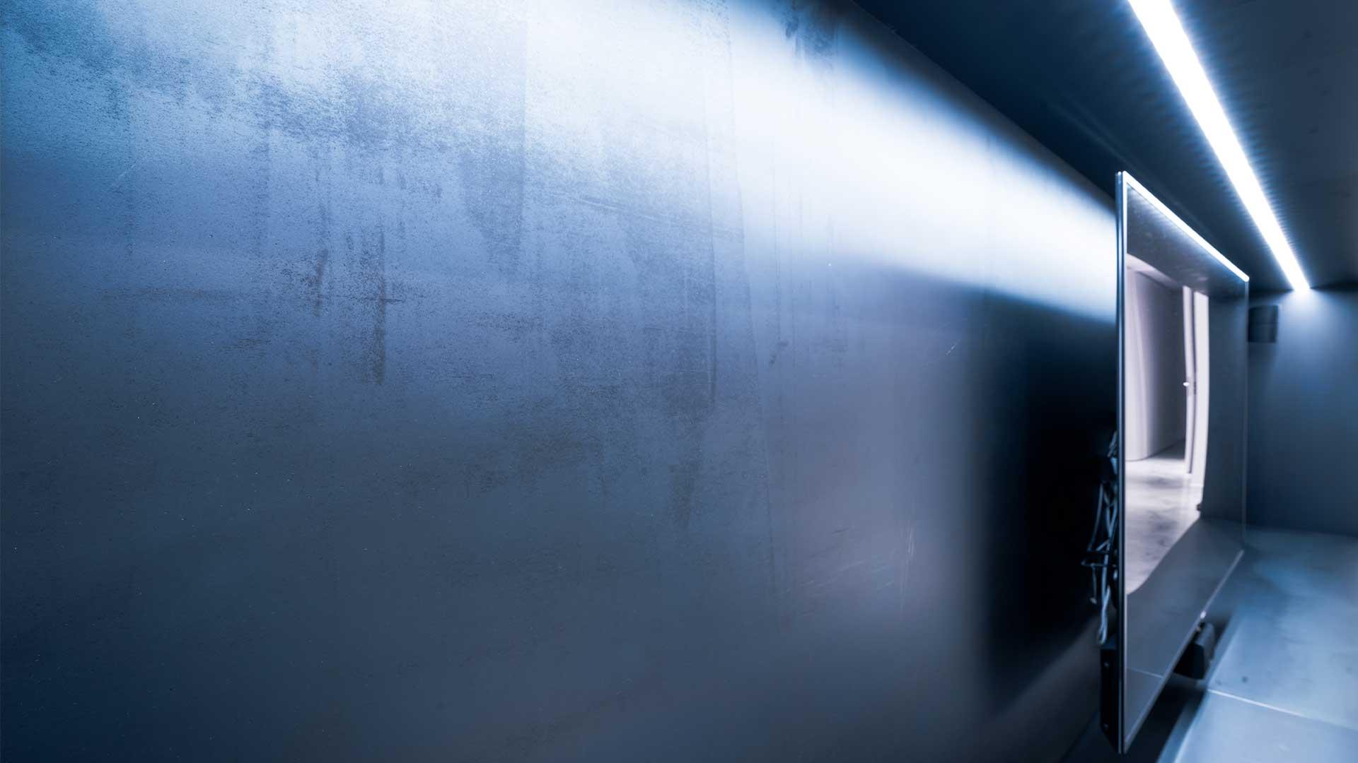 Nische aus schwarzem Stahl mit TV Gerät und nachhaltigem LED-Band zur Beleuchtung