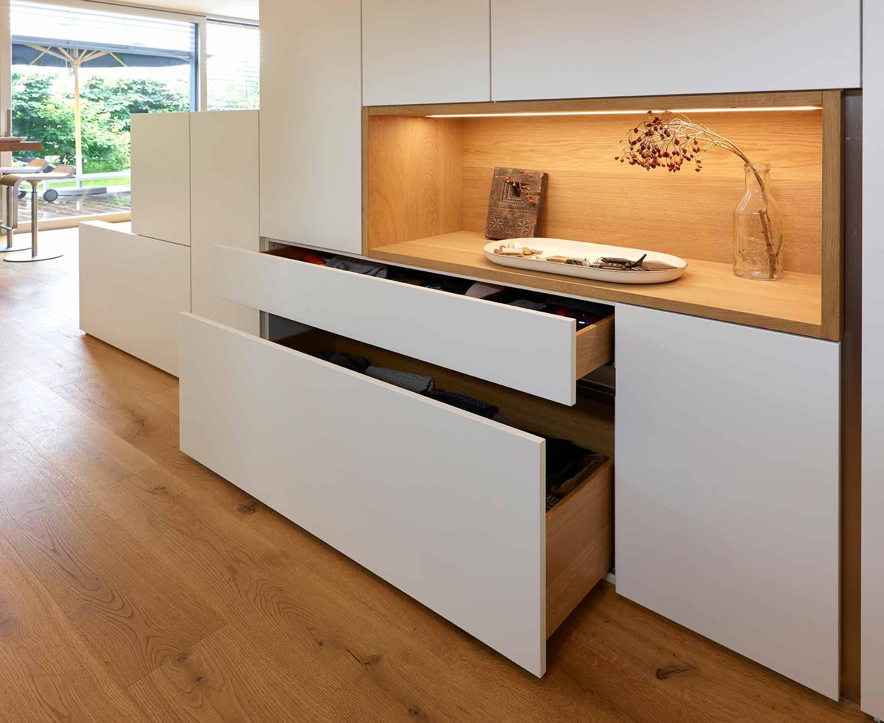 Küchendesign von VOIT in Eiche Natur mit BetonART und Edelstahl - Einbauschrank geöffnet mit Ablagefach aus Eiche