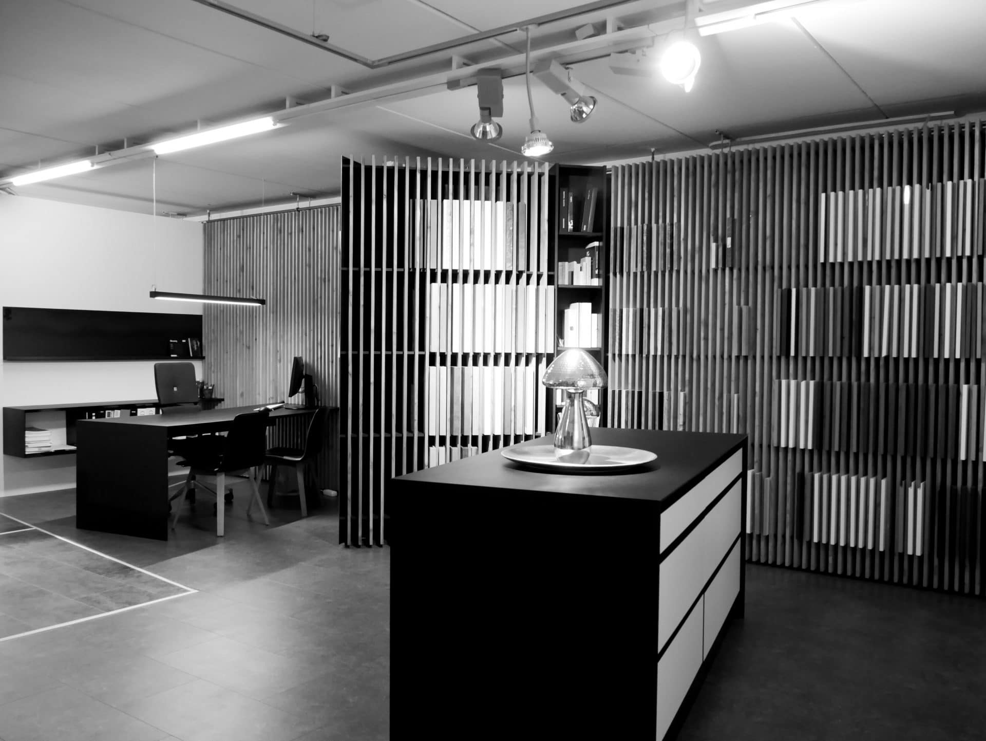 Showroom von Schreinerei und Planungsbüro VOIT in Reichertshausen, Besprechungsbereich mit Lammelenwand und einer Kommode im Vordergrund - Bild in schwarz-weiß