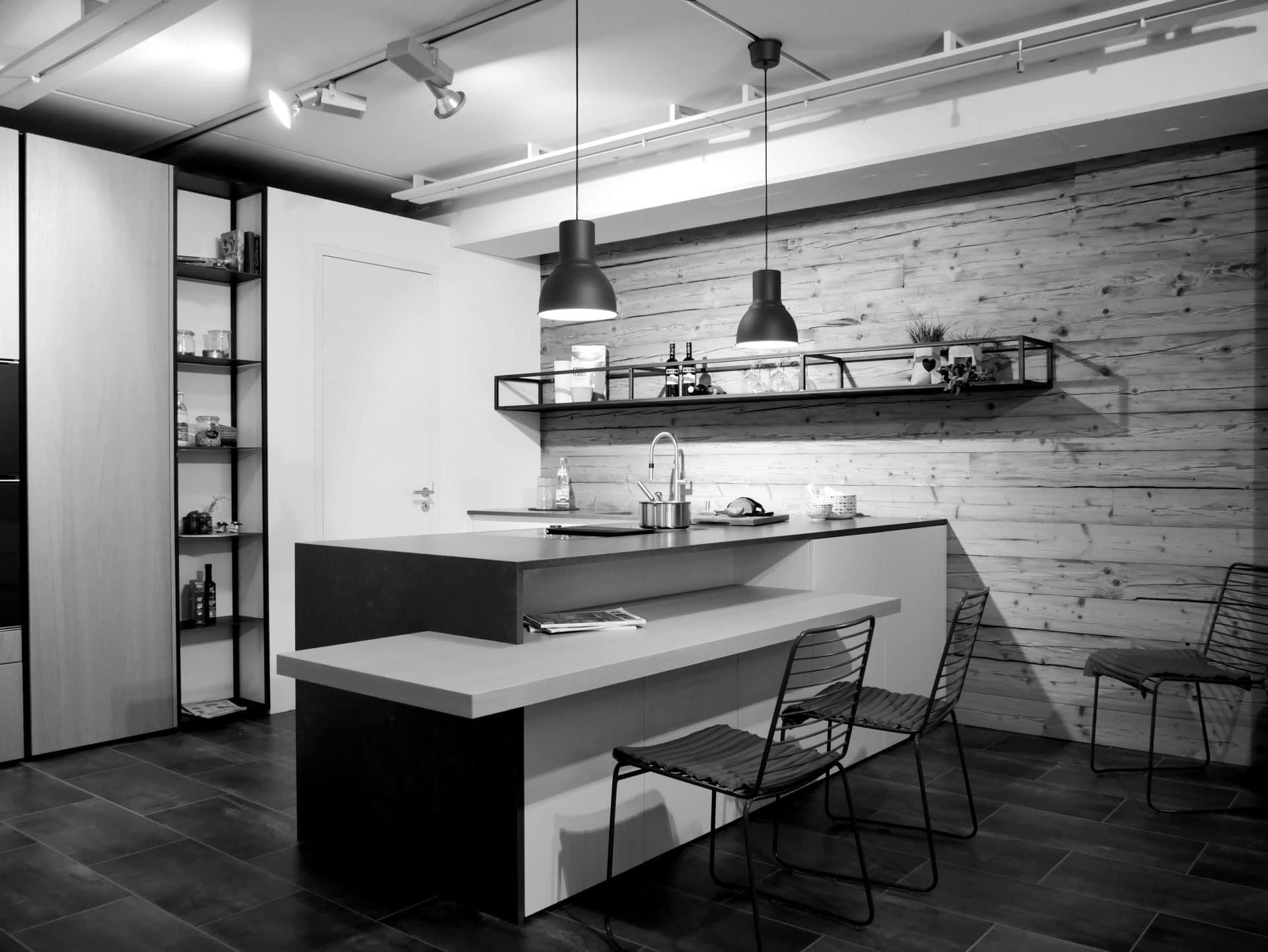 Showroom von Schreinerei und Planungsbüro VOIT in Reichertshausen, Designerküche aus Stein vor einer Echtholz Wand, davor 3 Stühle - Bild in schwarz-weiß