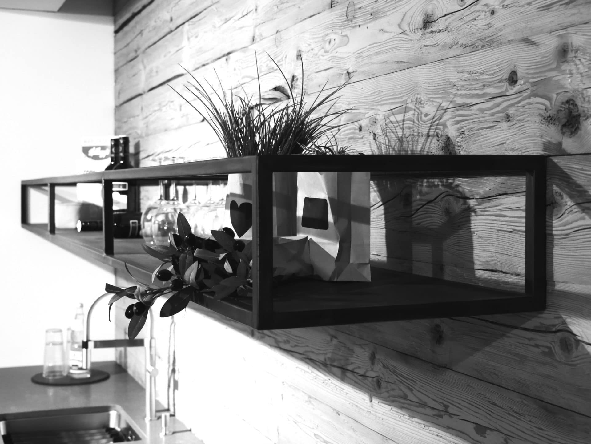 Showroom von Schreinerei und Planungsbüro VOIT in Reichertshausen, Nahaufnahme Regal mit Dekoration - Bild in schwarz-weiß