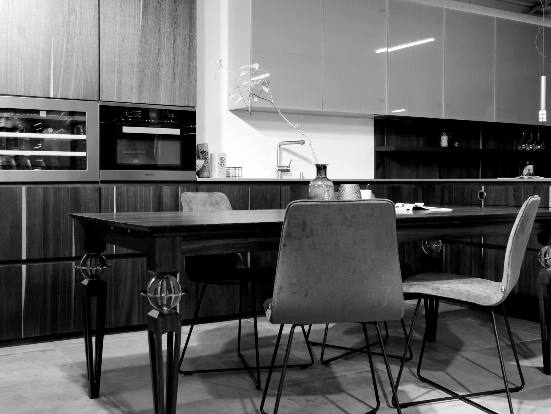 Showroom von Schreinerei und Planungsbüro VOIT in Reichertshausen, Designer Tisch, im Hintergrund Kücheneinbau mit Geräten und Naturholz Fronten - Bild in schwarz-weiß