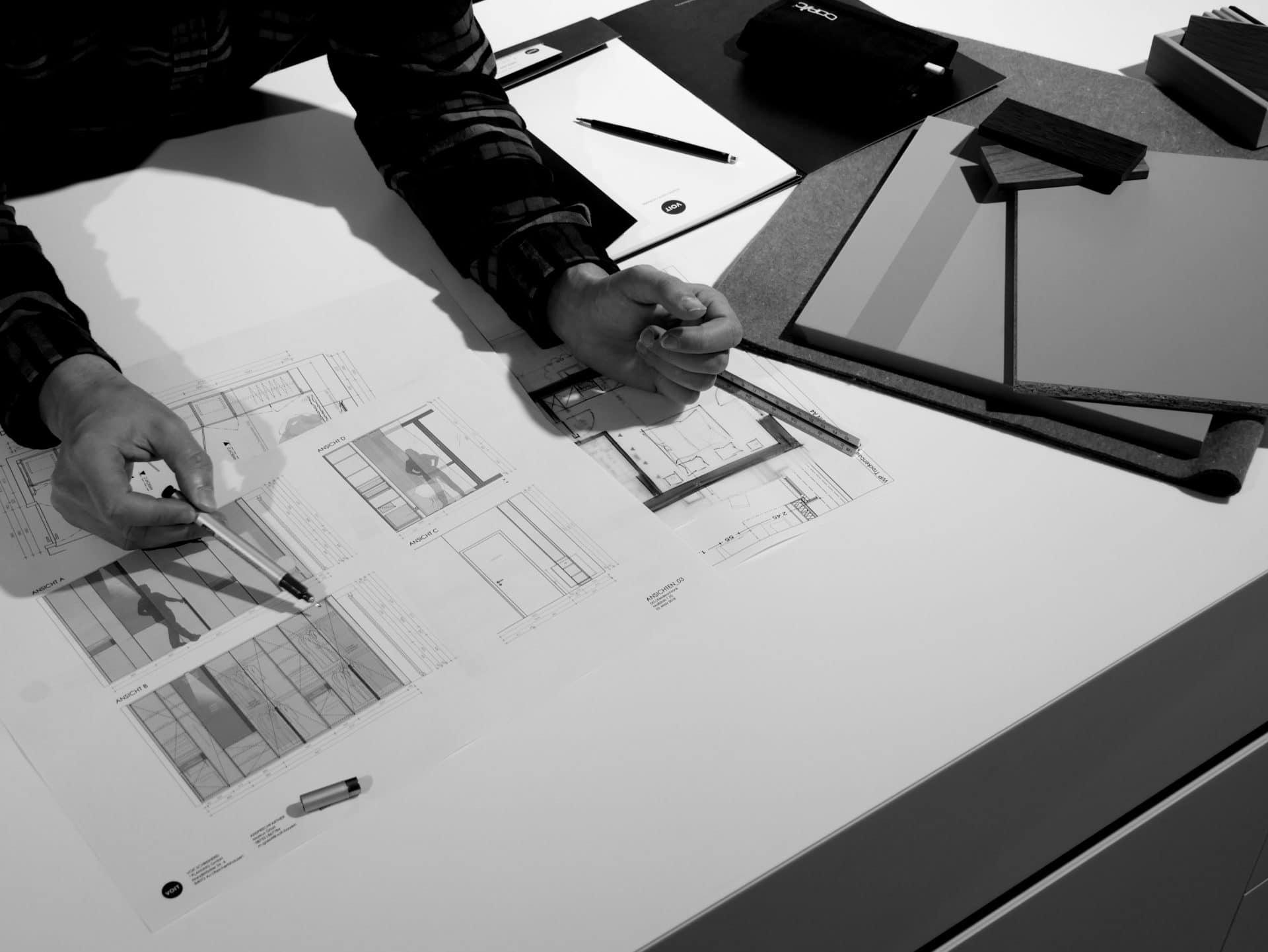 Innenarchitektur und Planung - Innenarchitekt entwirft eine neue Inneneinrichtung am Reißbrett mit Linea und Bleistift, daneben liegen verschiedene Material Muster