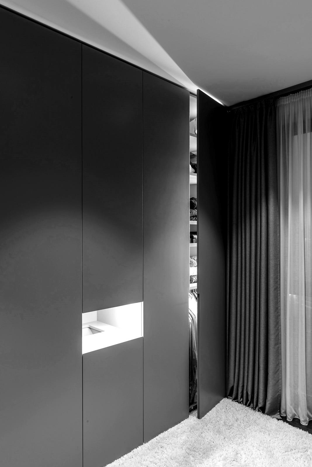 Innenarchitektur und Planung - Schwarze Inneneinrichtung im Schlafzimmer, halb geöffneter Kleiderschrank mit Wäscheeinwurf daneben