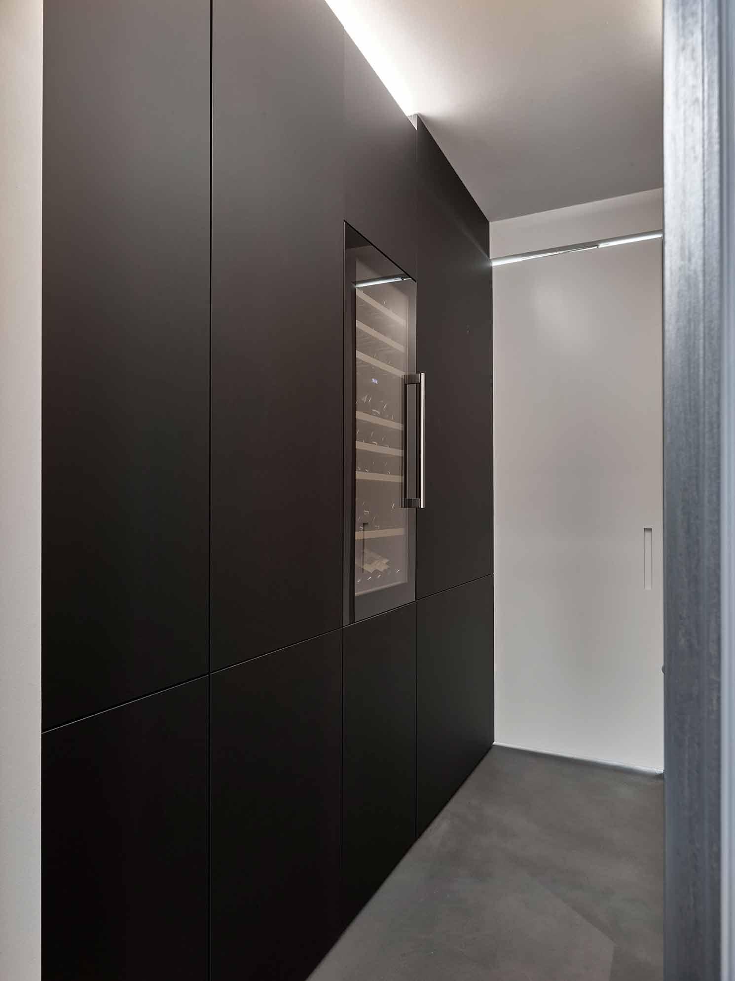 Küchendesign von VOIT aus geräucherter Eiche, Beton und Edelstahl - Blick in die Küche, links Schrankwand mit Weinkühler verbaut