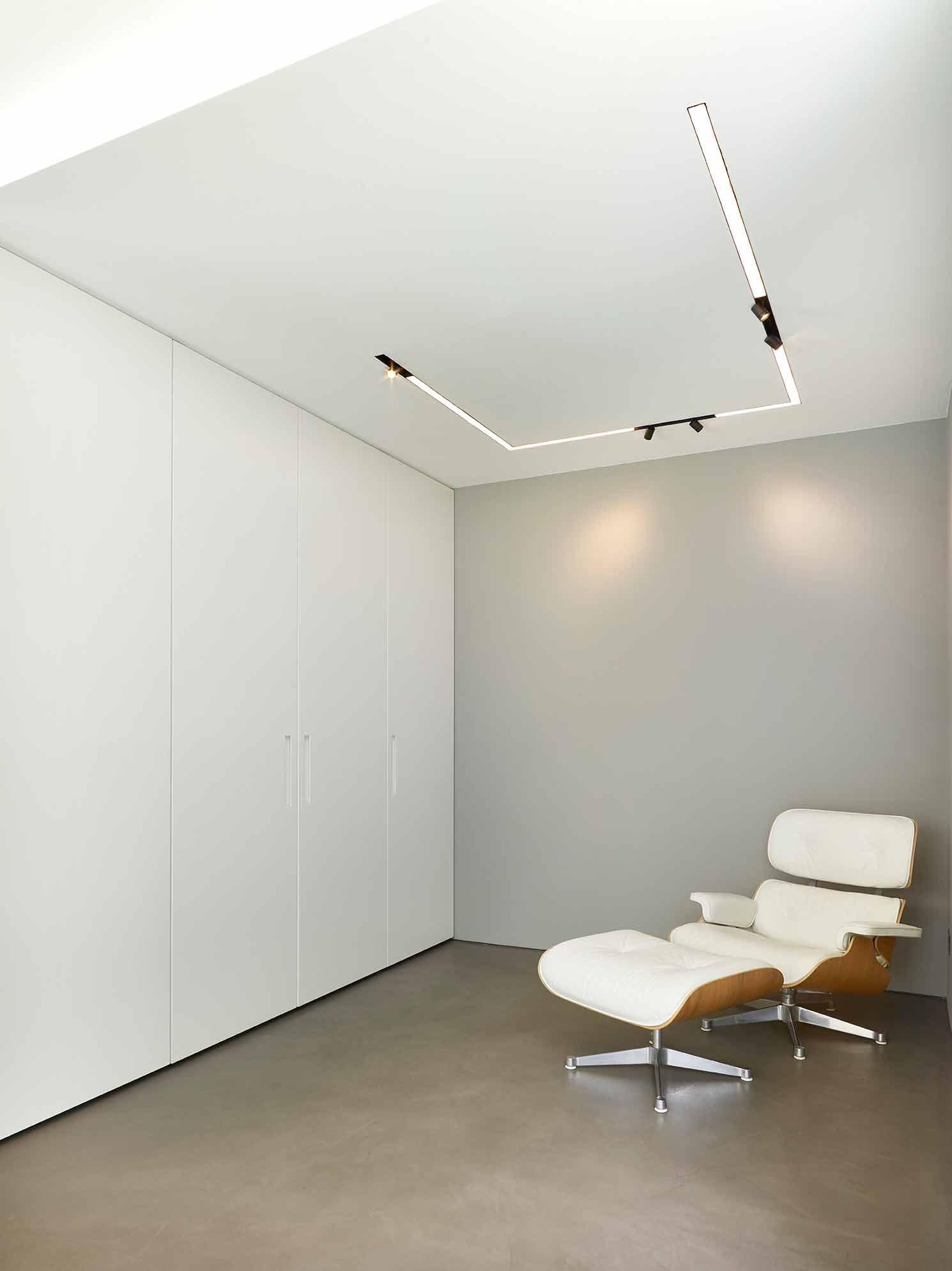 Küchendesign von VOIT aus geräucherter Eiche, Beton und Edelstahl - Versteckte Kaffeemaschine daneben ein Designerstuhl in weiß