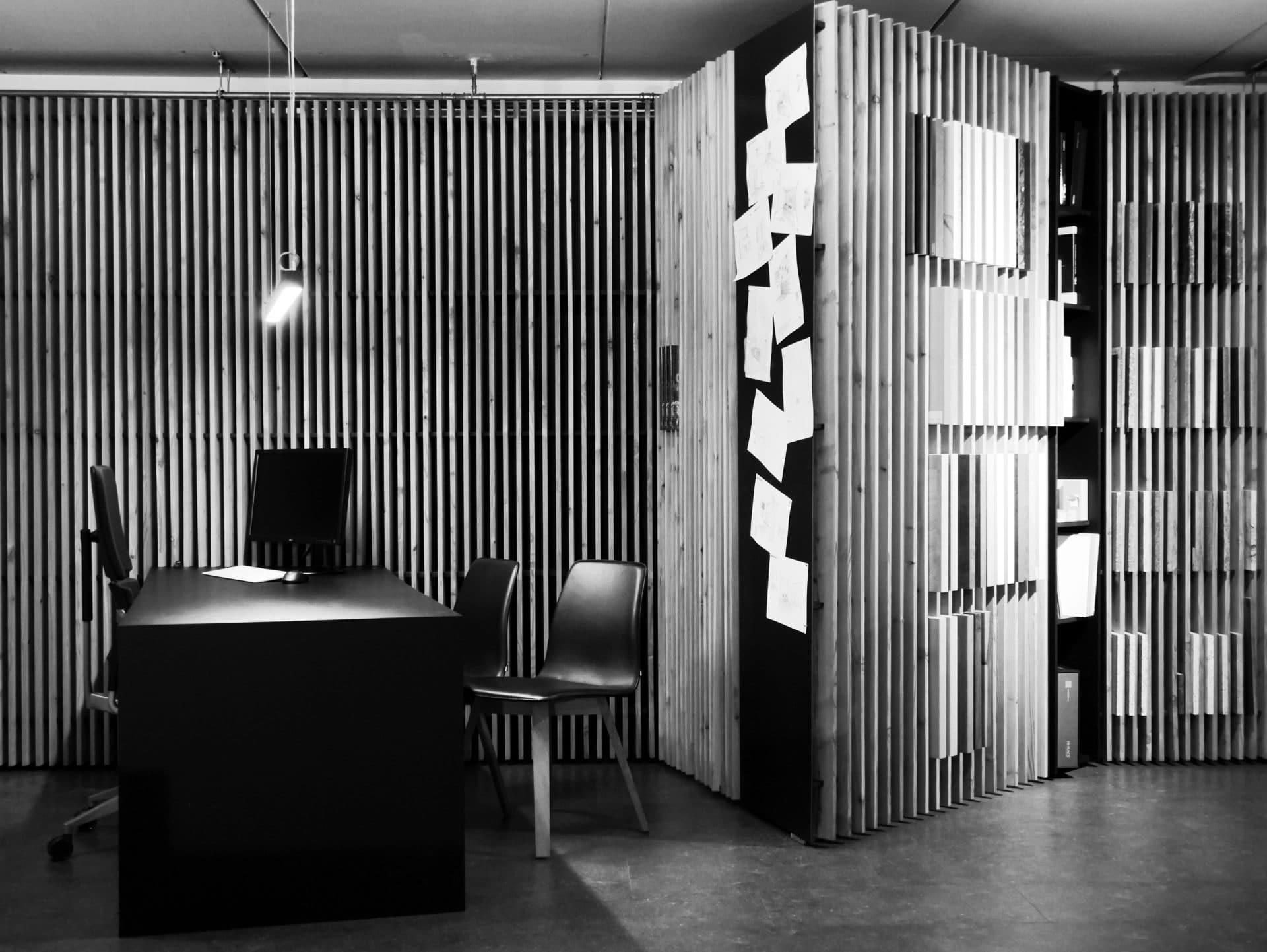 Showroom von Schreinerei und Planungsbüro VOIT in Reichertshausen, Besprechungsbereich mit Lammelenwand und Schreibtisch, davor 2 Stühle - Bild in schwarz-weiß