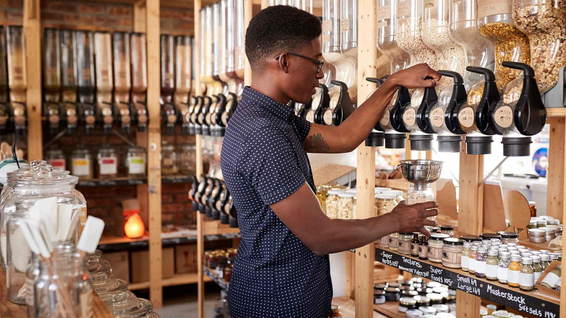 Mann füllt sich Müsli in einem Unverpackt-Laden selbst ab
