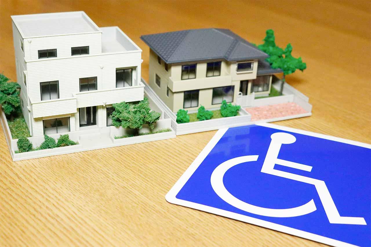 Modellhäuser mit einem Rollstuhlschild auf einem Tisch