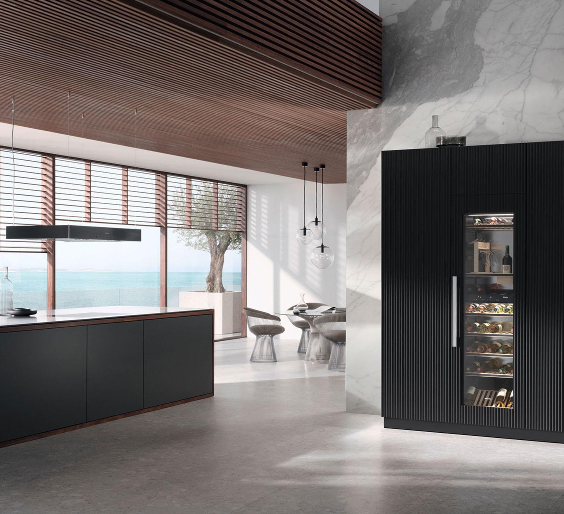 Miele Einbau-Weintemperierschrank KWT 6722 iGS in einer offenen Küche verbaut, im Hintergrund das Meer und eine Sonnenterasse