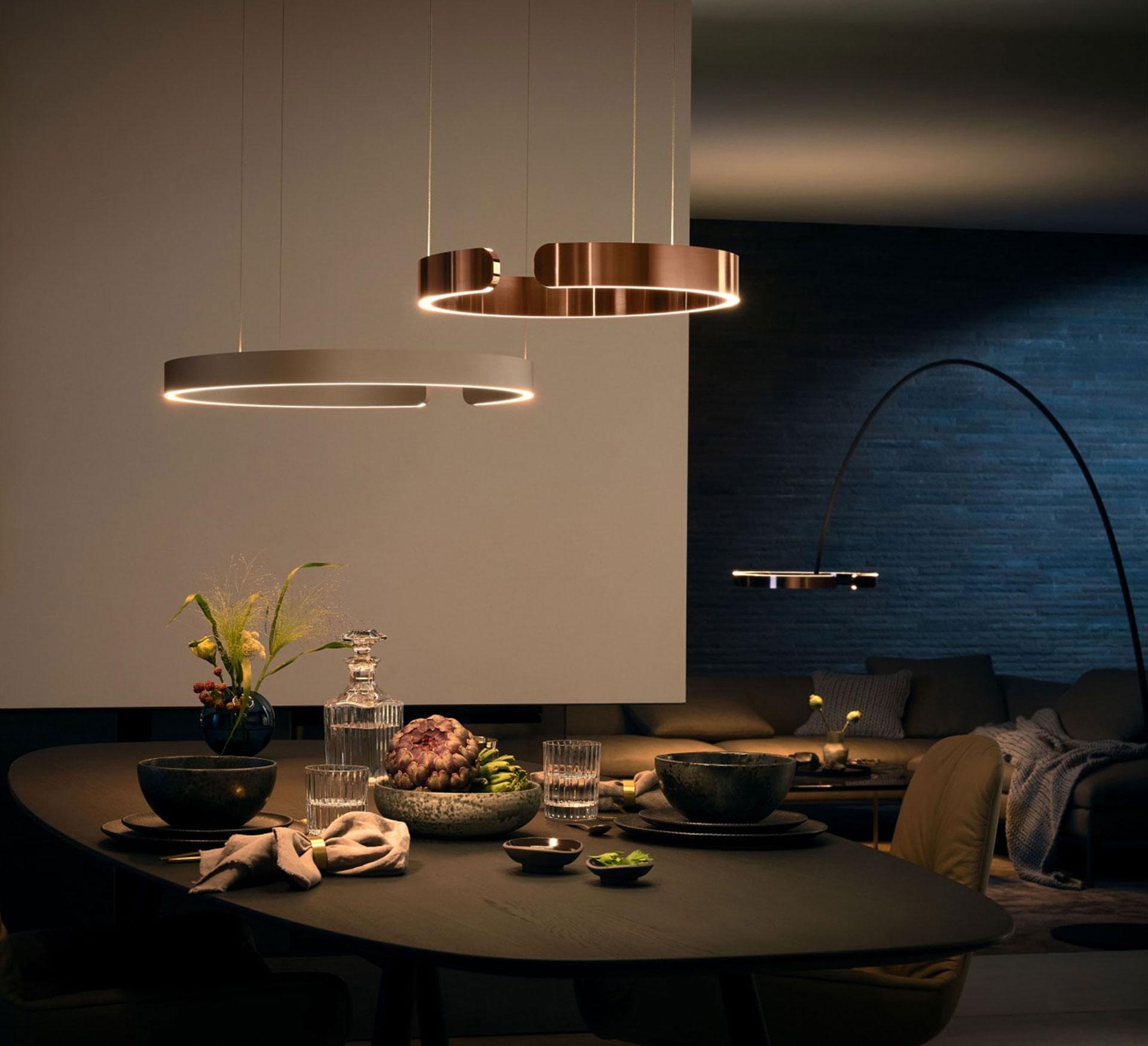 Zwei Occhio Mito sospeso von der Decke hängend, im Hintergrund eine Occhio Mito largo die den Wohnzimmertisch beleuchtet