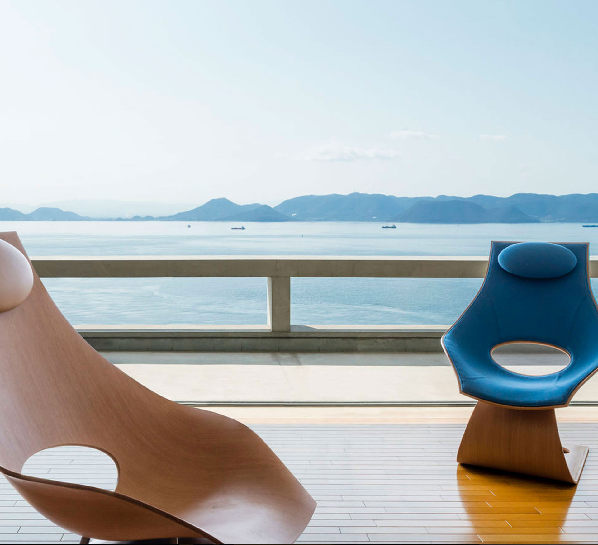 Zwei Carl Hansen & Søn - TA001P DREAM CHAIRS auf einer Sonnenterasse im Hintergrund Meer