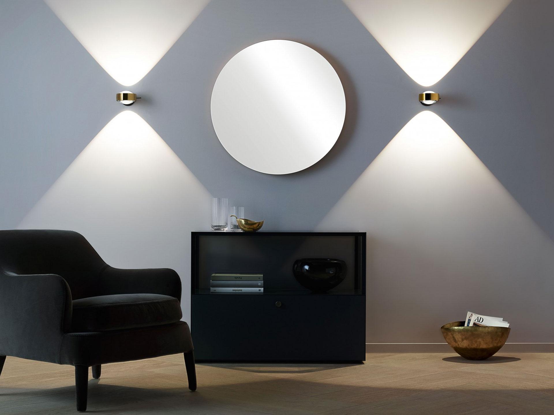 Zwei Occhio Sento verticale Designer LED-Wandleuchten an der Wand montiert, im Vordergrund ein schwarzer Sessel