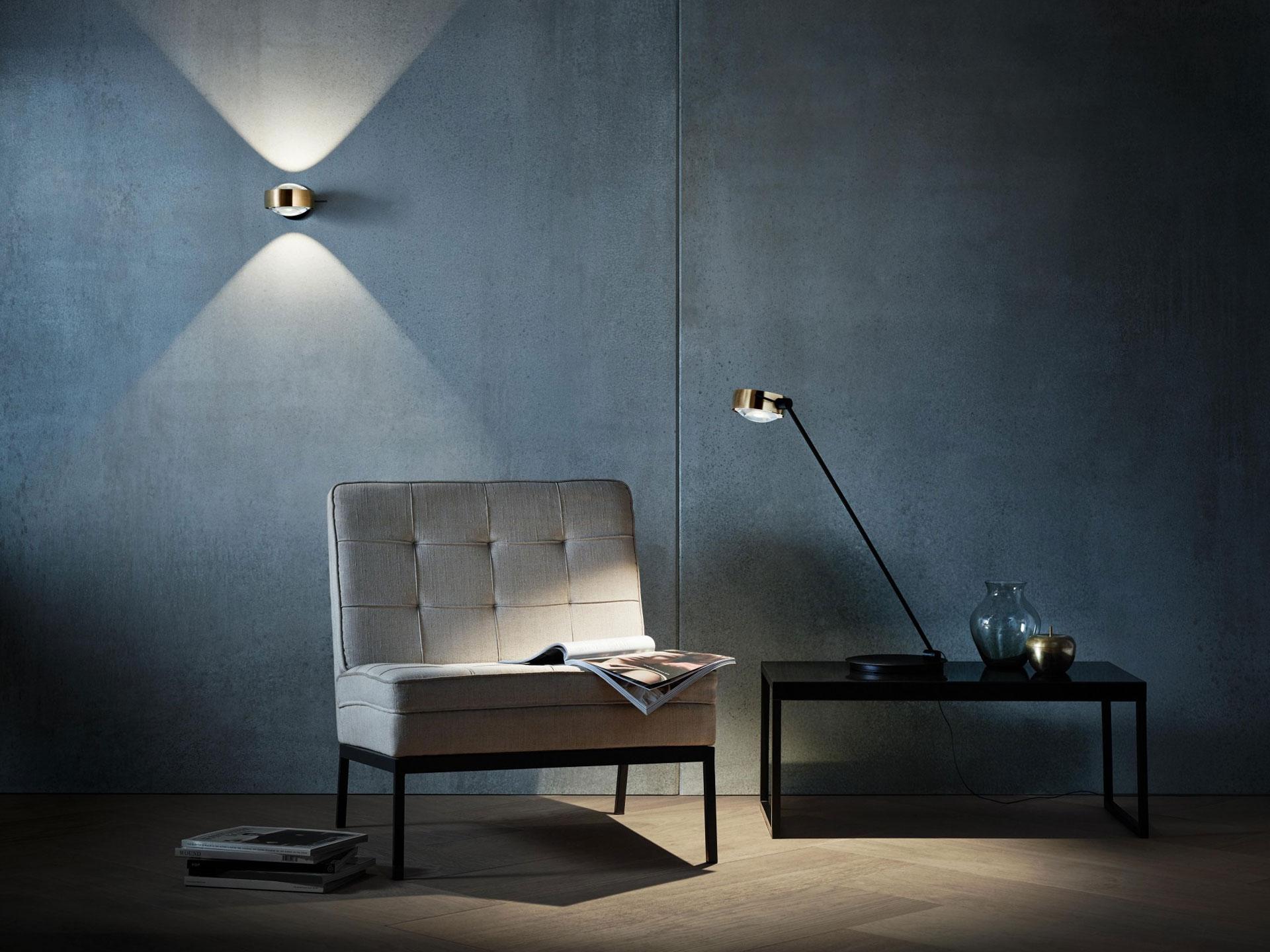 Designer LED-Wandleuchte Occhio Sento verticale über einer Sitzgelegenheit an der Wand