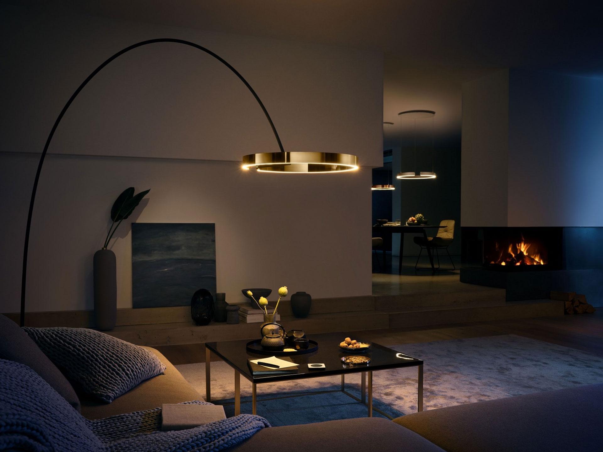 Designer LED Bogenleuchte Occhio Mito largo über dem Wohnzimmertisch hängend, im Hintergrund ein Kaminfeuer