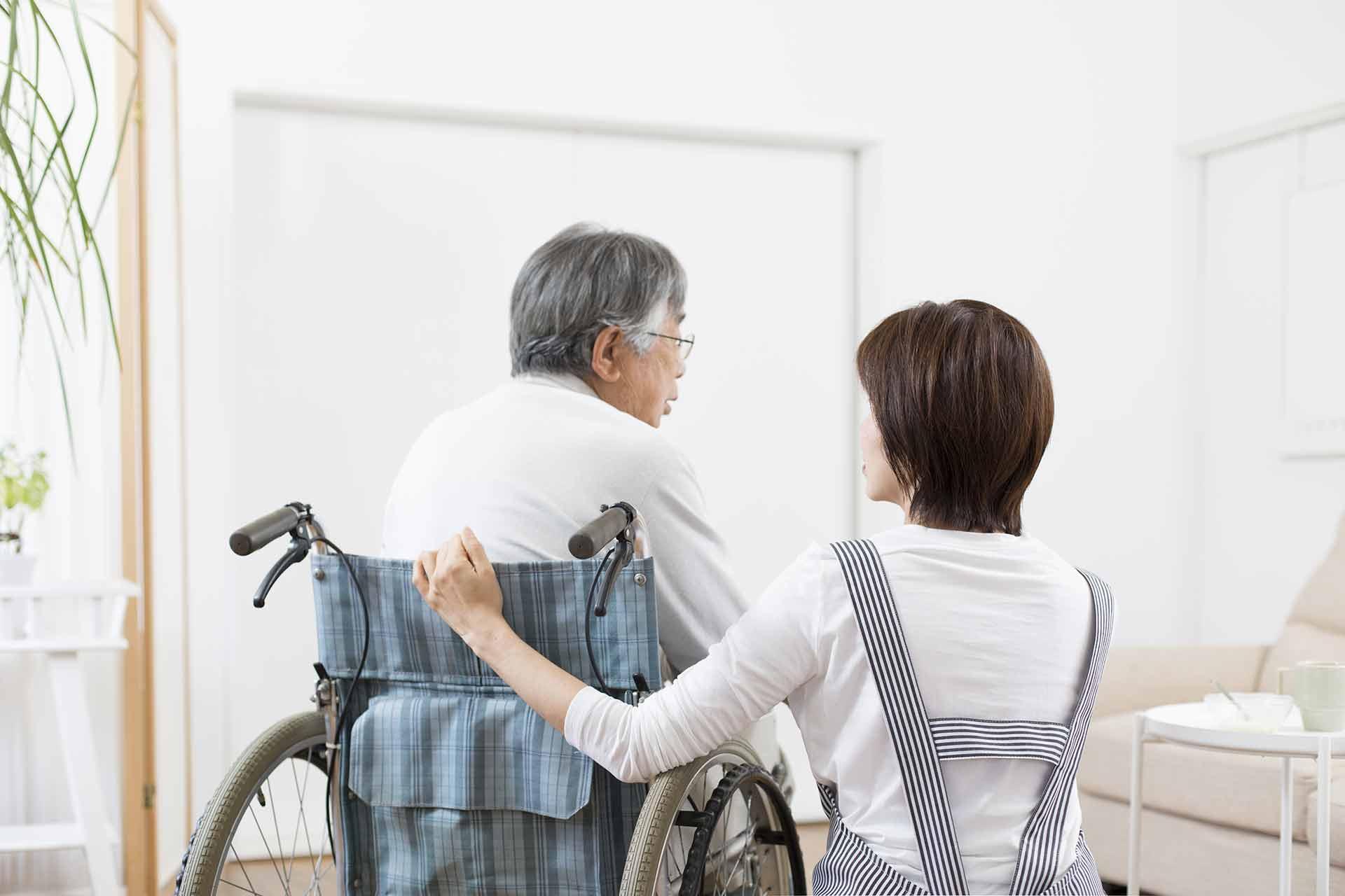 Pflegepersonal kümmert sich um Senioren im Rollstuhl in der barrierefreien Wohnung