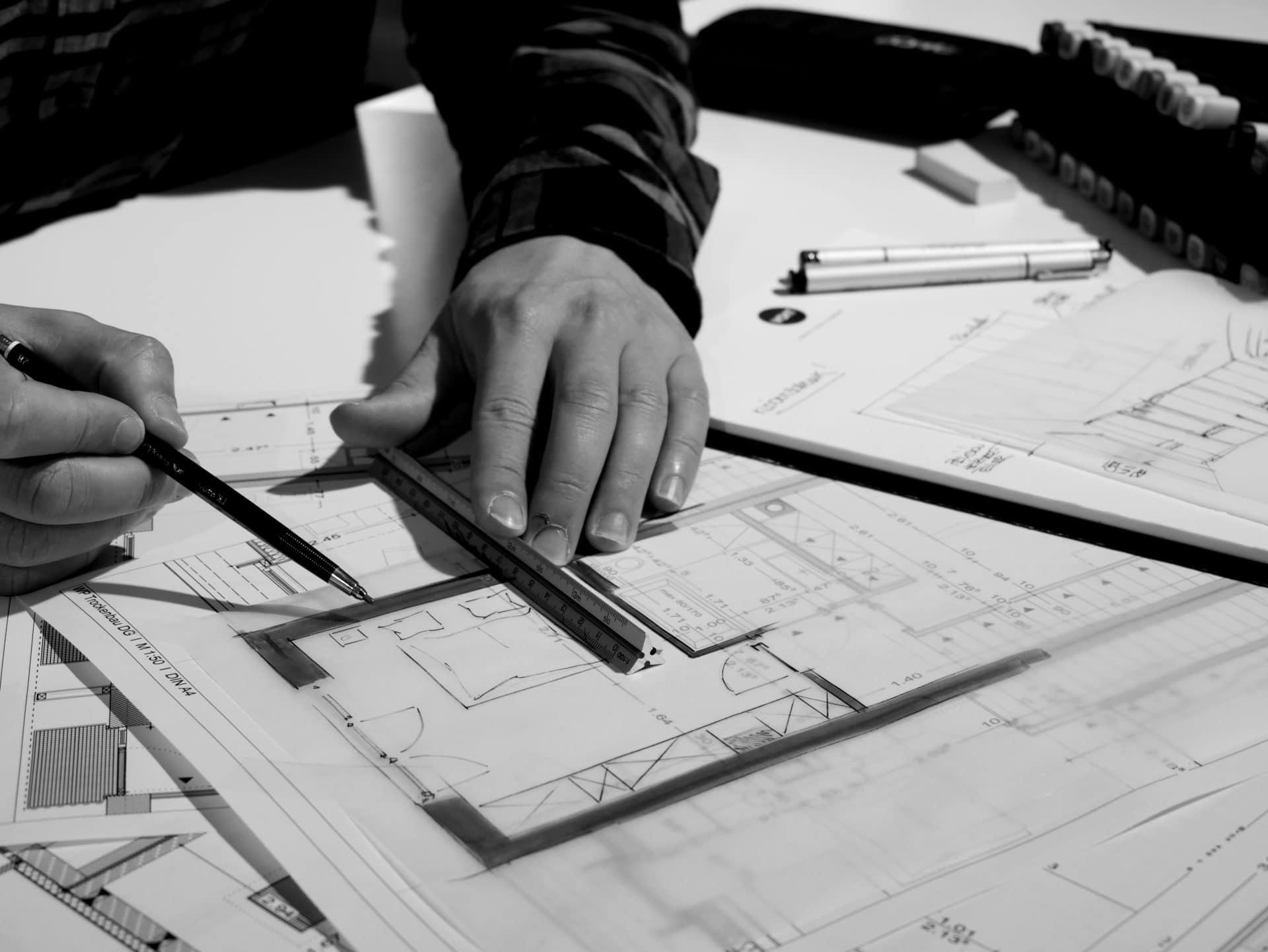 Innenarchitektur und Planung - Innenarchitekt entwirft eine neue Inneneinrichtung am Reißbrett mit Linea und Bleistift
