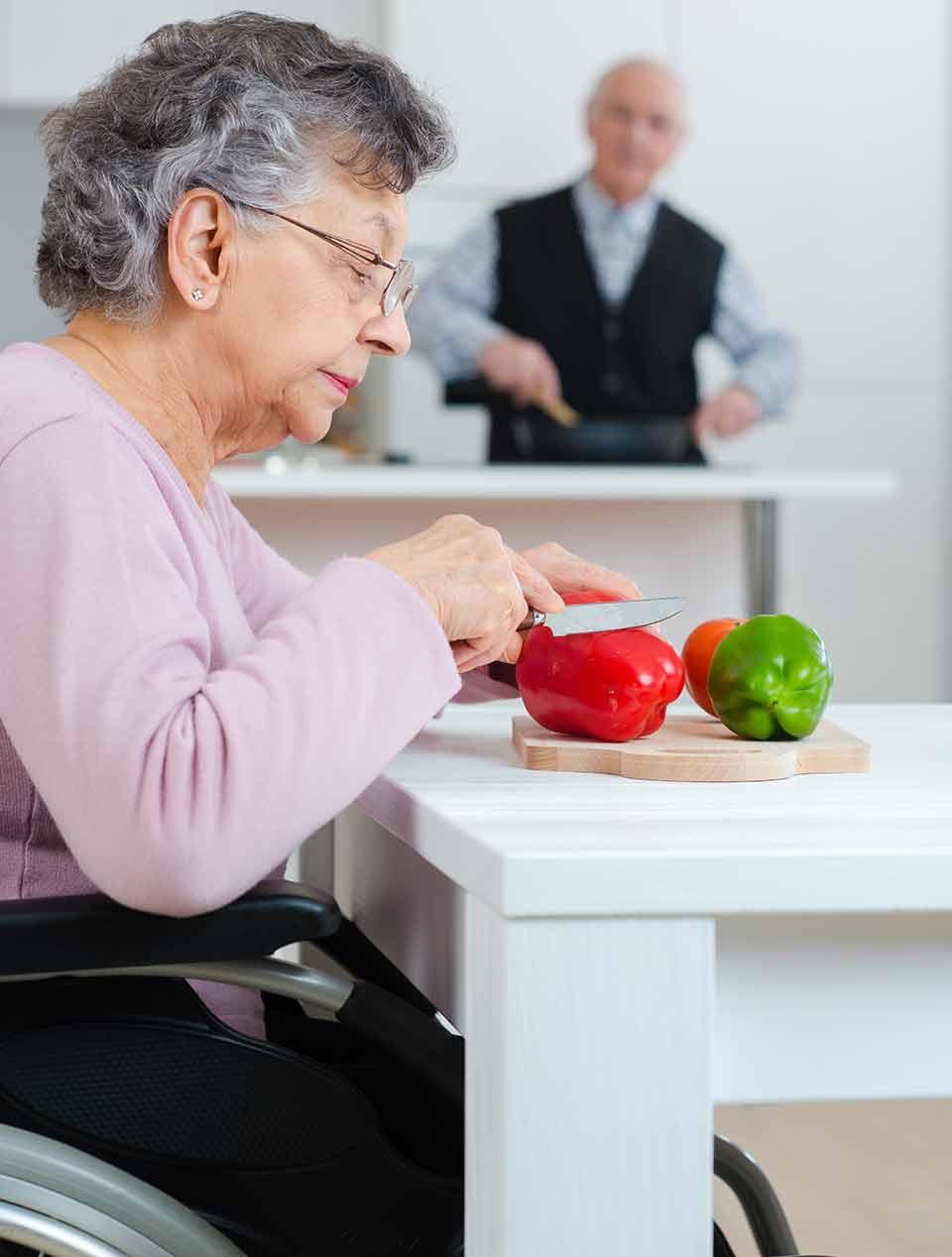 Seniorin sitzt im Rollstuhl in Ihrer barrierefreien Küche und schneidet Gemüse auf dem Esstisch, im Hintergrund kocht der Mann am Herd